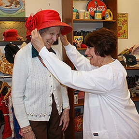 Nurse and Senior share a laugh while trying on a red hat in our boutique activity station