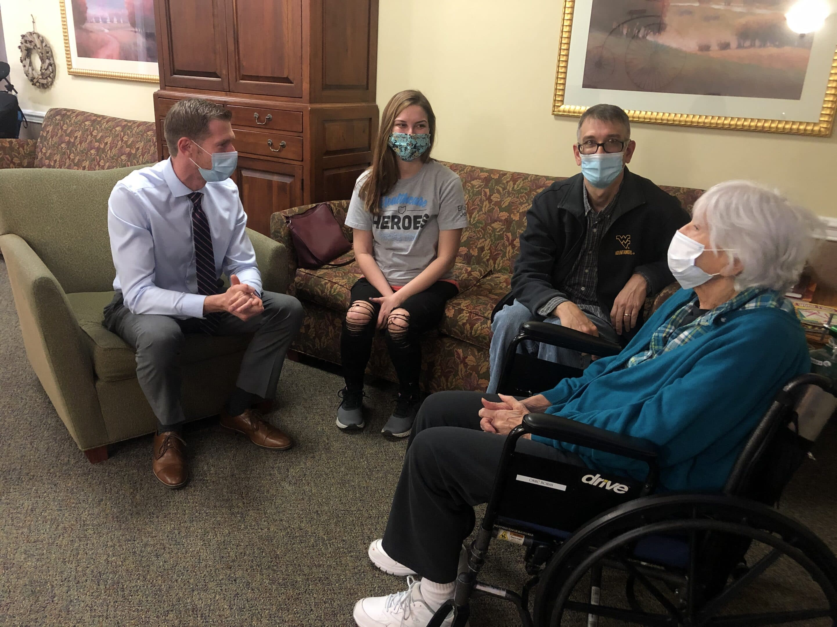 Four people sitting on couches talking. all are wearing masks.